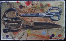 Two pairs of large scissors on splattered speckled background.